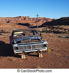 Junk car in desert.
