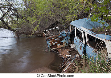 junk cars on river - consumerism and environment concept -...