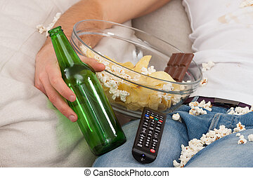Junk food, bottle and remote - A closeup of a man with a...