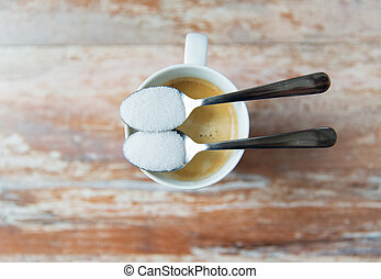 junk-food, diabetes and unhealthy eating concept - close up of white sugar on teaspoon and coffee cup