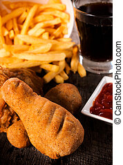 Junk food meal with fried chicken and french fries. ...