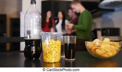 Junk food on the kitchen table. Chips, popcorn, soda. Young woman come closer and taking the bowl of chips away