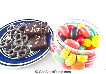 Junk Food - Plate of chocolate-covered pretzels and walnut-...