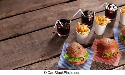 Junk food with cold drinks. Burgers and cola on table. So much calories. Freshness and taste.
