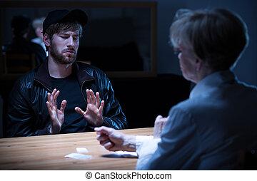 Junkie man interrogated by policewoman in a dark room