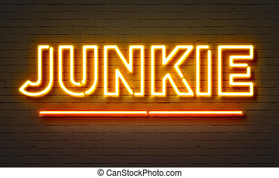Junkie neon sign on brick wall background.