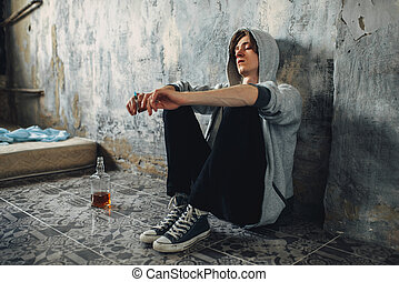 Junkie with syringe sitting on floor after dose
