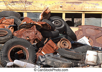 Old tires and wheels in a junkyard.