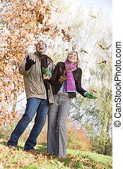 junte ao ar livre, tocando, em, folhas, e, sorrindo,...