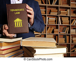 Jurist holds TENNESSEE LAW book. Tennessee residents are subject to Tennessee state and U.S. federal laws