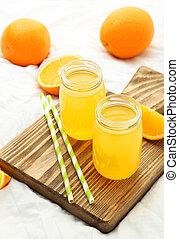 jus orange, planche découper, bouteille