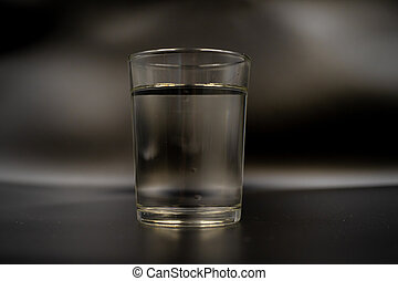 Just a glass of water on a dark wooden table. Mineral water in a glass on a black background. A glass with water