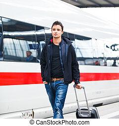 Just arrived: handsome young man walking along a platform at...