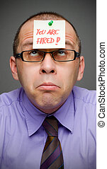 Just fired - Middle aged businessman with note on his head