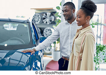 just imagine us on the road. portrait of happy african couple checking out a car