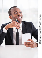 Just inspired. Cheerful young African man in formalwear holding a note pad and pen while sitting at the table