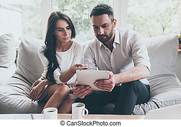 Just look at this! Confident young couple sitting together on couch and looking at digital tablet