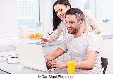 Just look at this! Handsome young man working on laptop and smiling while his cheerful girlfriend bonding to him and pointing monitor