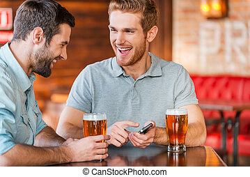Just look at this photo! Two happy young men in casual wear drinking beer in pub while one of them holding smart phone and pointing it with smile