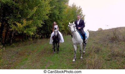 Long-haired female in white wedding dress and male in black suit are smiling and riding two horses while walking along edge of autumn forest. Colorful trees and grass, blue sky.