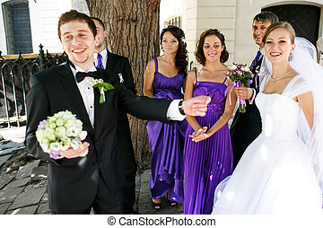 Just married couple has fun while walking with their friends