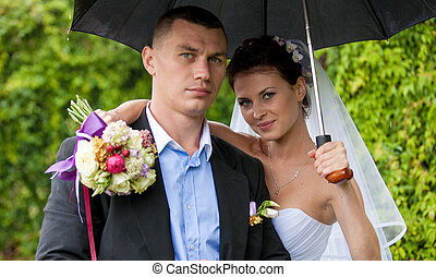 Just married couple hugging under umbrella