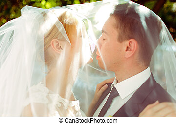 Just married couple kiss standing under a veil in the shine of morning sun