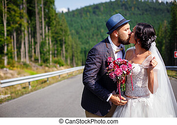 just married couple kissing on the road