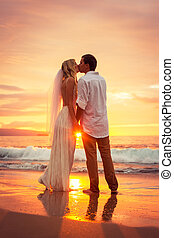 Just married couple kissing on tropical beach at sunset