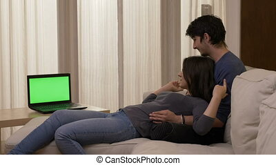 Just married couple sitting on a white sofa watching a movie on the laptop with green screen at home hugging and kissing at home in the living room