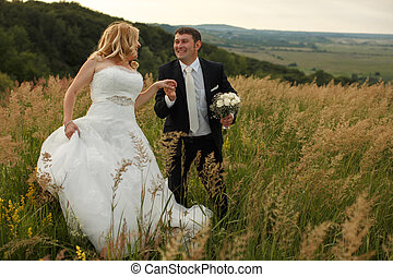 Just married couple smiles walking in a high grass