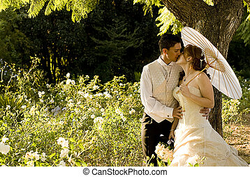 just married couple standing and kissing in white flower bed under a tree in nature on a sunny day