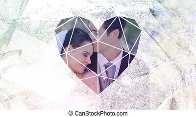 Animation of a happy Caucasian just married couple seen through a white heart shaped window in the foreground
