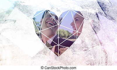 Animation of a happy just married Caucasian couple on a motorbike seen through a white heart shaped window in the foreground