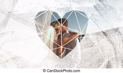 Animation of the side view of a Caucasian just married couple kissing on a beach with the bridal veil blowing towards the camera, seen through a white heart shaped window in the foreground