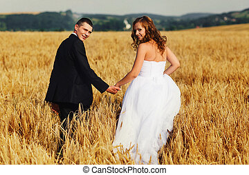 Just married couple turn around walking across the field on a sunny day