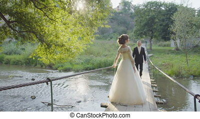 Just married couple walking in the city, bridge uhd - Just...