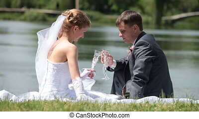 just married couple with champagne - bride and groom drink...