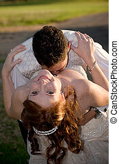 just married couple with groom kissing bride in the cleavage on a sunny day