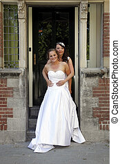 just married lesbian pair holds each other on doorstep of old city hall