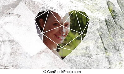 Animation of the side view of a just married Caucasian bride smelling her bouquet and turning to camera smiling, seen through a white heart shaped window in the foreground