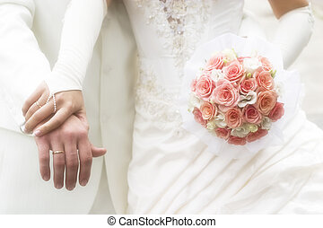 just married - young couple in wedding wear with bouquet of roses. Soft-focused image in high key