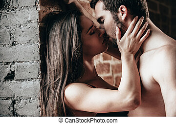 Just one kiss. Side view of beautiful young loving couple kissing while standing near brick wall