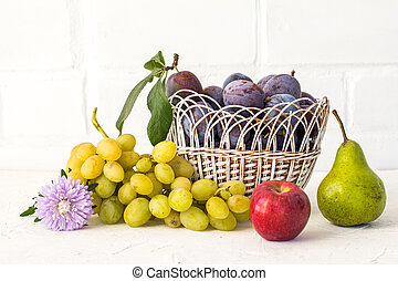 Just picked plums and grapes in wicker basket on white backdrop.