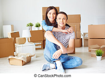 Happy young couple sitting on the floor of new house surrounded by boxes