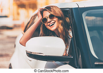 Just road ahead. Beautiful young cheerful women looking at camera with smile while sitting in her car