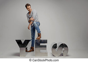 Just say ?yes?! Handsome young men stepping on the metal letter and looking away while isolated on grey