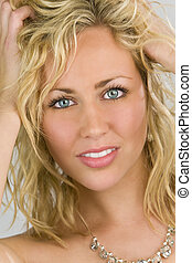 Studio shot of a stunningly beautiful blue eyed model running her fingers through her blond hair