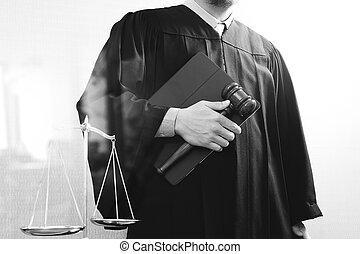 justice and law concept. Male judge in a courtroom with the gavel and balance scale and holy book and digital tablet computer