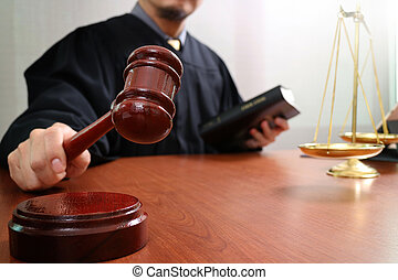 justice and law concept. Male judge in a courtroom with the gavel and working with smart phone and brass scale on wood table